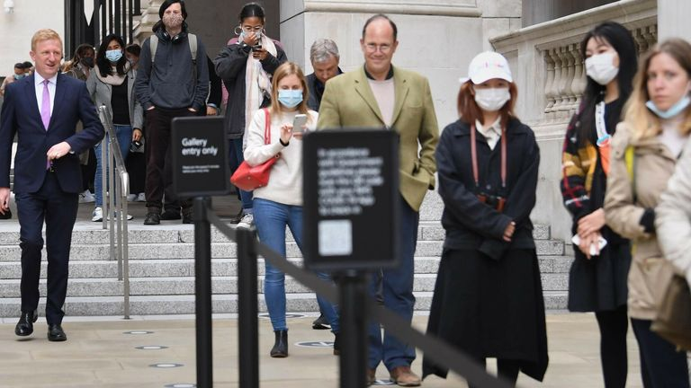 People queueing to get into the National Portrait Gallery in London are photo-bombed by Culture Secretary Oliver Dowden (L)
