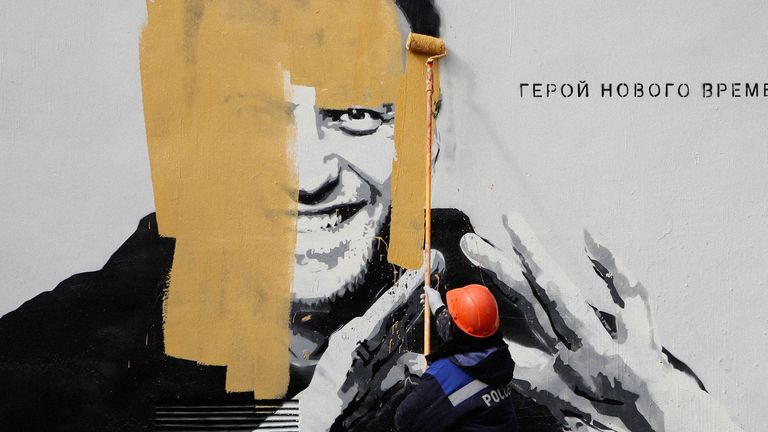 Russian authorities paint over a mural showing opposition leader Alexei Navalny in St Petersburg