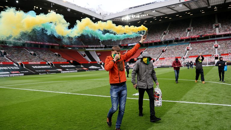 Soccer Football - Manchester United fans protest against their owners before the Manchester United v Liverpool Premier League match - Manchester, Britain - May 2, 2021 Manchester United fan with a flare on the pitch in protest against their owners before the match Action Images via REUTERS/Carl Recine