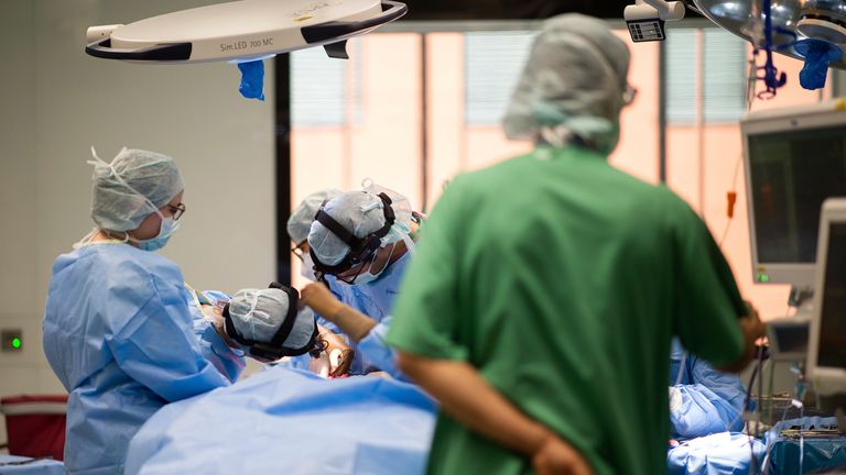 27 April 2021, North Rhine-Westphalia, Essen: A team of doctors and surgical assistants stand around a patient during an operation in the ENT operating theatre at the University Hospital. The new construction of the operating wing for eye and ENT operations cost almost 70 million euros. According to the University Hospital, these are currently the most modern operating theatres in Germany and Europe. Photo by: Jonas G'ttler/picture-alliance/dpa/AP Images