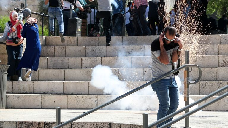 People react to a stun grenade fired by police officers during the demonstration