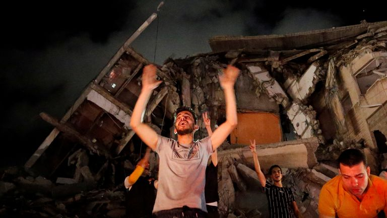 People cheer outside a damaged building in Gaza City after the truce began