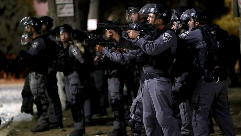 Palestinians react as Israeli police fire stun grenades during clashes at the compound that houses Al-Aqsa Mosque, known to Muslims as Noble Sanctuary and to Jews as Temple Mount