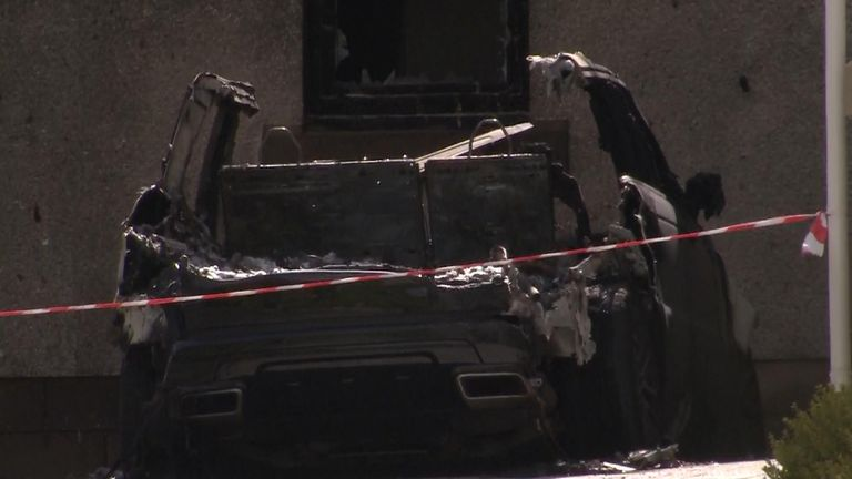 A burned out car at the scene