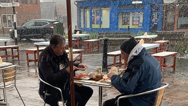Two men eating their meal at Yangaz Bistro Grill in Cranleigh, Surrey at 0800 on Monday morning during wintry conditions. Pub-goers will need to wrap up warm on Monday, as chilly temperatures are forecast for the first day of outdoor hospitality reopenings in England. Picture date: Monday April 12, 2021.