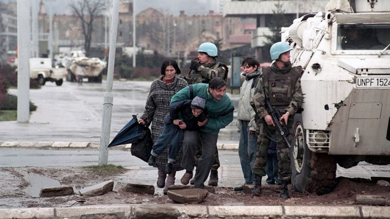 The residents of Sarajevo take cover from sniper fire behind a United Nations Protection Force (UNPROFOR) armoured vehicle in this 1993 file photo. Genocide, siege and massacre are for many people in Bosnia more than just words on Radovan Karadzic's indictment. They represent years of suffering, dead friends and nightmares that will always haunt them. To match feature WARCRIMES-KARADZIC/LEGACY REUTERS/Danilo Krstanovic/Files (BOSNIA AND HERZEGOVINA)