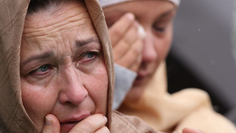 Bosnian Muslim women weeps near the remains of a relative during a mass funeral for 70 Bosnian Muslims killed at the beginning of Bosnian war, in the village of Kozarac near Prijedor, 120 kms northwest of Bosnian capital of Sarajevo, on Wednesday, July 23, 2008. The victims were killed in July 1992 during an offensive by Bosnian Serbs that left more than 4,000 missing persons who were buried in numerous mass grave around town of Prijedor. Radovan Karadzic, wanted for genocide and crimes during t