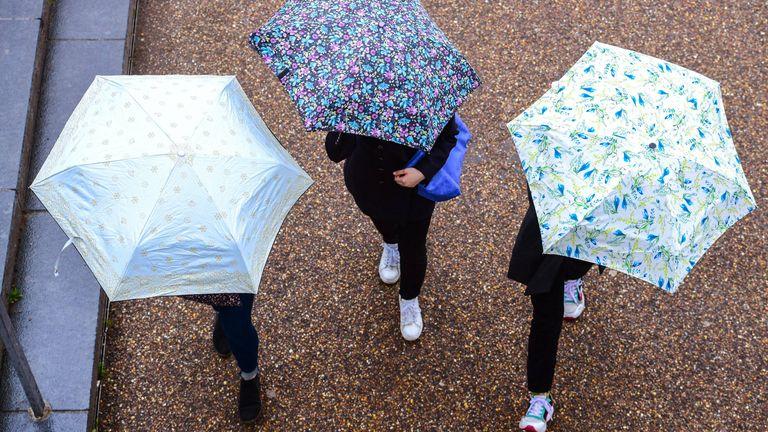 People with umbrellas walk under the Millennium Bridge in London