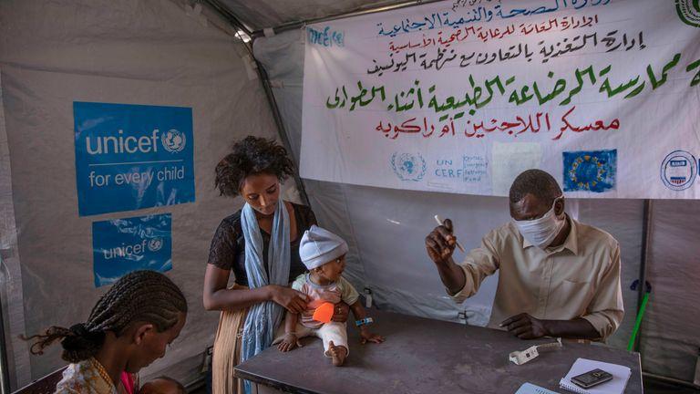 Tigray women who fled the conflict in Ethiopia...s Tigray region, take shelter inside a UNICEF tent, as Filippo Grandi, U.N. High Commissioner for Refugees, visits Umm Rakouba refugee camp in Qadarif, eastern Sudan, Saturday, Nov. 28, 2020. (AP Photo/Nariman El-Mofty)