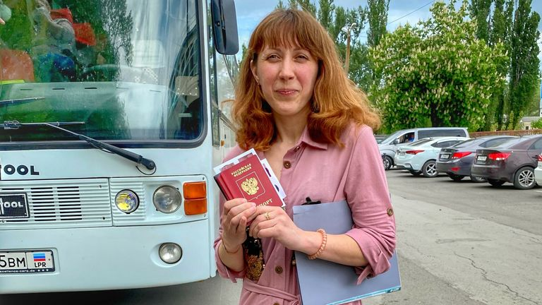 A young woman poses proudly with her new passport