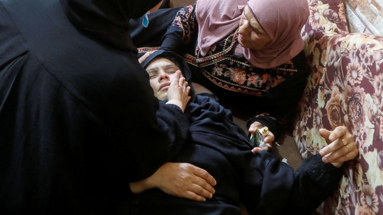 The mother of Saeed Yusuf Muhammad Oudeh is looked after by relatives after she fainted during her son's funeral