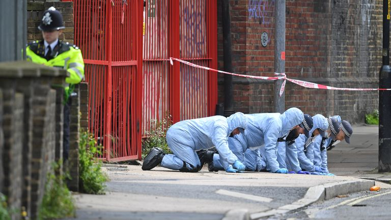 Forensic officers search a street near the scene of the incident in Peckham, south London