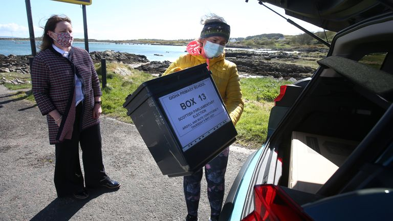 Shona Barton, from the returning office team at Argyll and Bute Council hands over equipment to presiding officer Morven Beagan (R) for use at a polling station on the Isle of Gigha