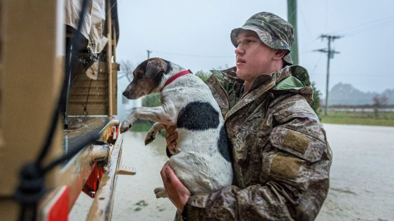 A soldier in the NZ Army rescues a dog during flooding in New Zealand's South Island. Pic: NZ Defence Force