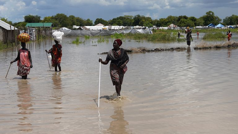 Women wade through floodwaters after Nile broke dikes in Pibor