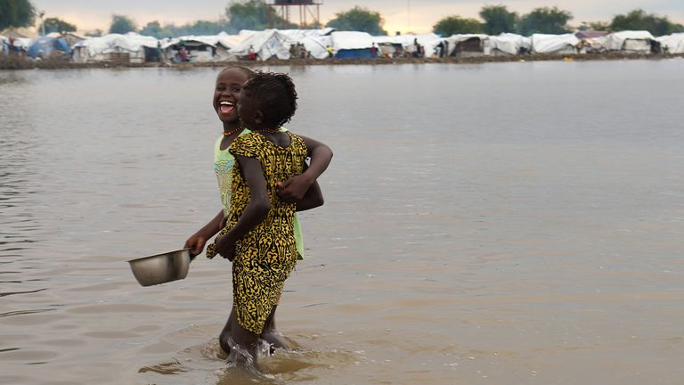 Displaced children wade through floodwaters after the River Nile broke the dykes in Pibor last year