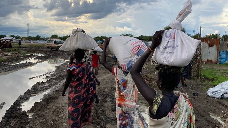 Food and supplies are carried home by Sudanese men and women