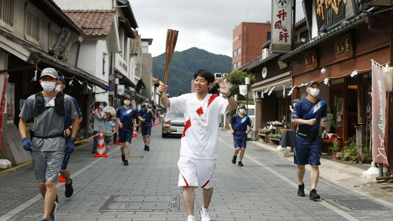 A Tokyo Olympic torch relay participant runs in the Shimane Prefecture town of Tsuwano, western Japan, on May 15, 2021. (Kyodo via AP Images) ==Kyodo