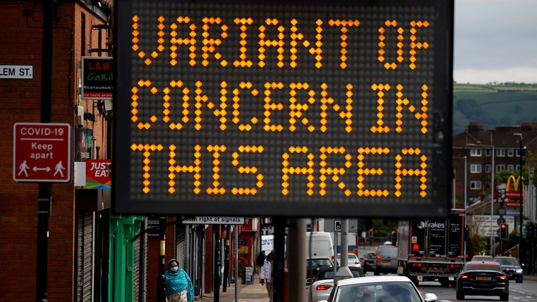 FILE PHOTO: A woman walks past an information sign amid the outbreak of the coronavirus disease (COVID-19) in Bolton, Britain, May 17, 2021. REUTERS/Phil Noble/File Photo