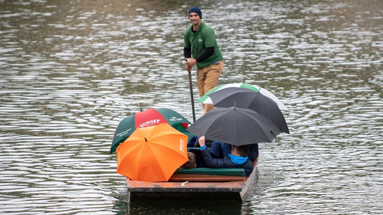 People shelter from the rain while trying to enjoy punting in Cambridge