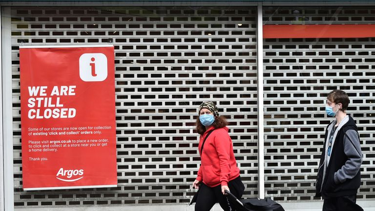 Members of the public walks past a still closed sign outside Argos in Leicester city centre in Leicester, England, Tuesday June 30, 2020. The British government has reimposed lockdown restrictions in the English city of Leicester after a spike in coronavirus infections, including the closure of shops that don...t sell essential goods and schools. (AP Photo/Rui Vieira)