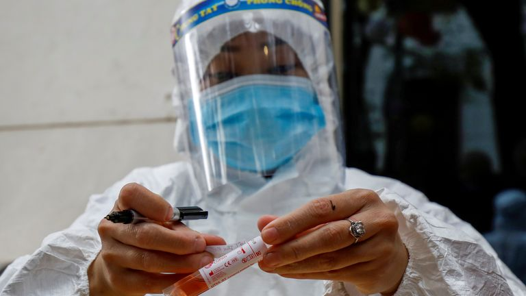FILE PHOTO: A health worker labels a test-sample tube during the coronavirus outbreak in Hanoi, Vietnam, January 29, 2021. REUTERS/Kham/File Photo