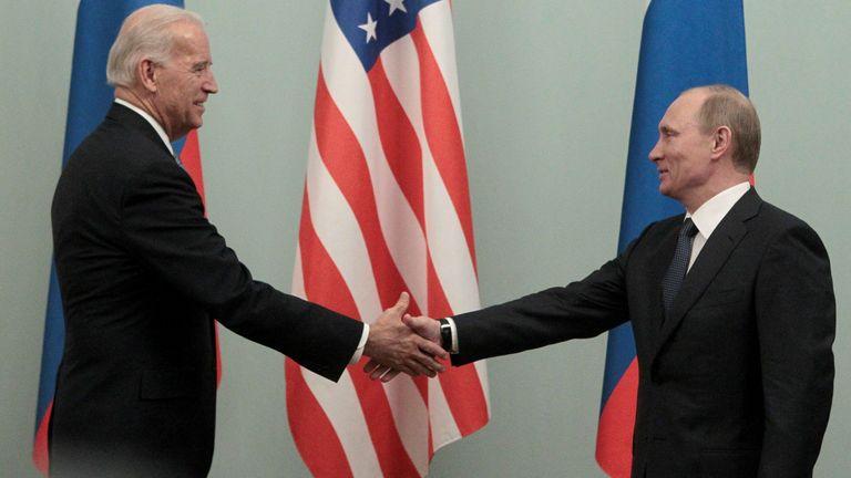 Vladimir Putin (R) shakes hands with then vice president Joe Biden in Moscow in 2011