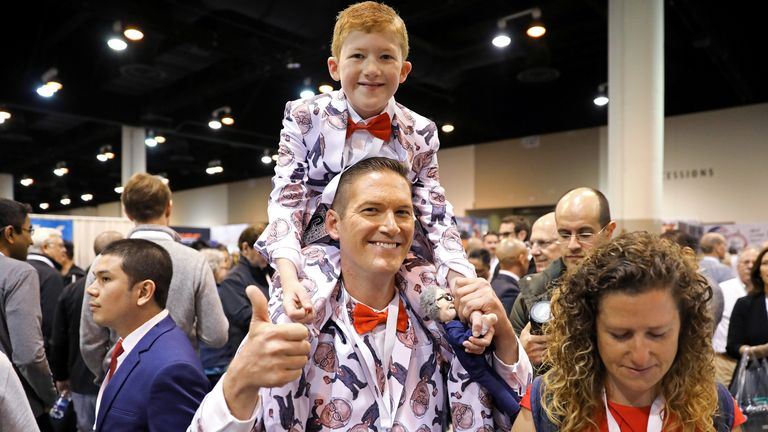 Ray Renk holds his 10-year-old son Benjamin as they wear matching custom-made suits printed with a caricature of Berkshire Hathaway Chief Executive Warren Buffett at the annual shareholder meeting in Omaha, Nebraska, U.S., May 4, 2019
