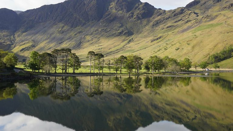 Trees reflected in the water at Buttermere in the Lake District, Cumbria, on Tuesday