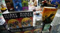 Customers stand next to Harry Potter books at a bookstore in Beijing August 16, 2007. Chinese students have worked their magic on Harry Potter, translating the latest instalment within hours of release of the English version, state media said