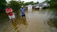 Danny Gonzales, right, stands in front of his flooded house with his neighbor Bob Neal, upset with power company trucks driving though the flooded neighborhood pushing water back into his home, after Tropical Storm Claudette passed through, in Slidell, La., Saturday, June 19, 2021. (AP Photo/Gerald Herbert)