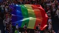 FILE - In this file photo dated Saturday, July 6, 2019, participants of the annual LGBTQ pride parade carry the emblematic rainbow flag in Madrid, Spain. The Spanish Cabinet on Tuesday June 29, 2021, passed a draft bill on LGBTQ rights that will seek parliamentary approval to allow transgender people over 16 years old to freely change their gender and name in the official registry without doctors or witnesses intervening in the process. (AP Photo/Manu Fernandez)