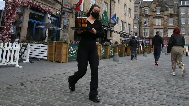 A server carries a tray of drinks from a pub in the Grassmarket in Edinburgh, as beer gardens, non-essential shops, restaurants and cafes, along with swimming pools, libraries and museums in Scotland reopen today after lockdown restrictions have eased. Picture date: Monday April 26, 2021.