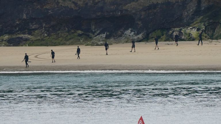 Police officers search the beach with metal detectors at Carbis Bay, Cornwall, ahead of the G7 summit in Cornwall. Picture date: Monday June 7, 2021.
