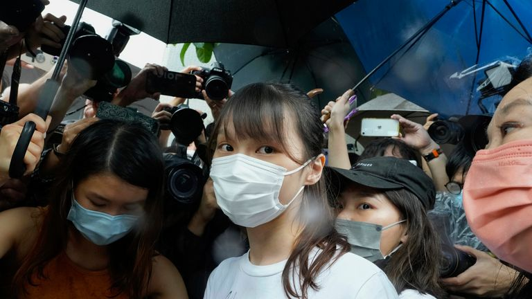 Agnes Chow, center, a prominent pro-democracy activist who was sentenced to jail last year for her role in an unauthorized protest, is released on Saturday, June 12, 2021. Chow rose to prominence as a student leader in the now defunct Scholarism and Demosisto political groups, alongside other outspoken activists such as Joshua Wong and Ivan Lam. (AP Photo/Vincent Yu)