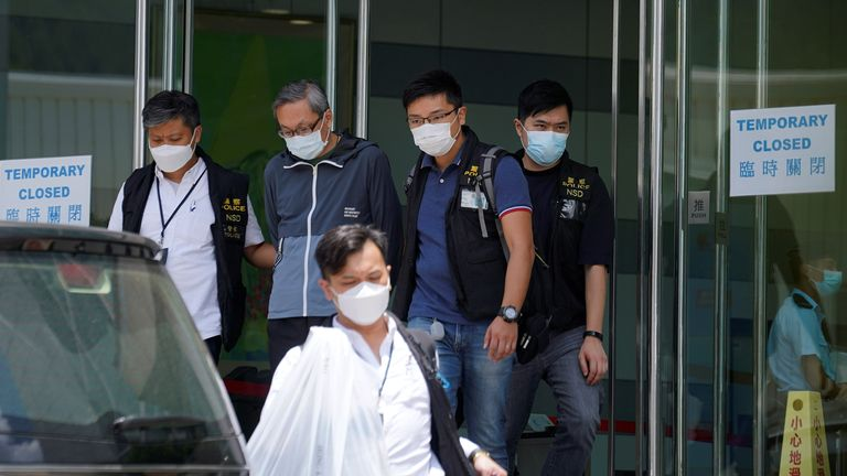 Police officers escort Apple Daily's Chief Executive Officer Cheung Kim-hung from the building