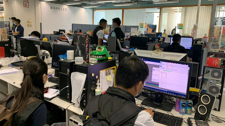 Police officers are seen in Apple Daily's newsroom