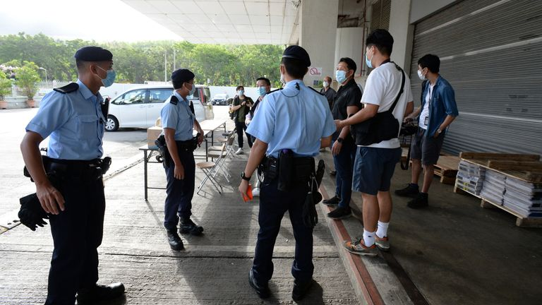Police officers are seen at the headquarters of Apple Daily