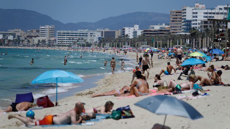 People sunbathe on the beach of Arenal