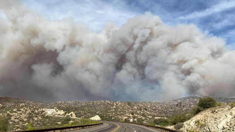 Smoke plumes rise from a blaze as a wildfire rages on in Arizona