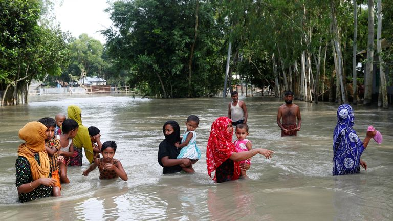 Flood-affected people are seen on water as they wait for a boat to cross a stream in Jamalpur, Bangladesh