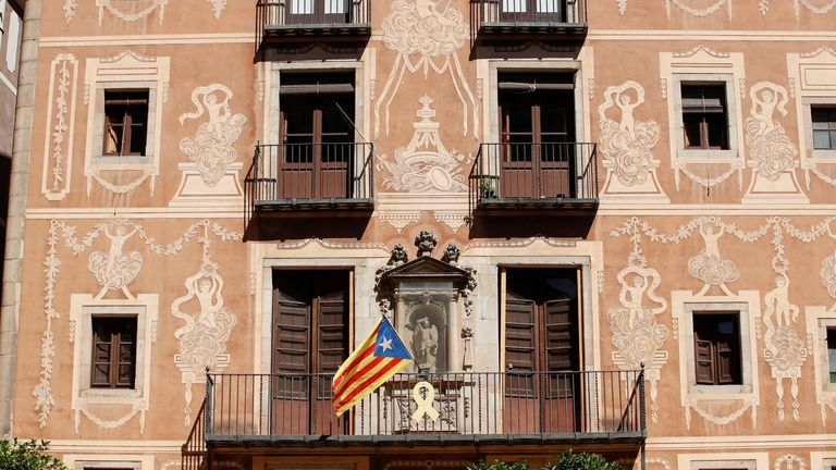 A yellow ribbon hangs from a balcony next to a Catalan separatist flag in Barcelona on Tuesday