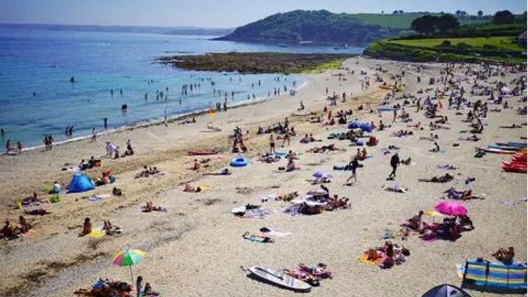 People enjoy the sunshine on Gyllyngvase Beach near Falmouth in Cornwall on Sunday