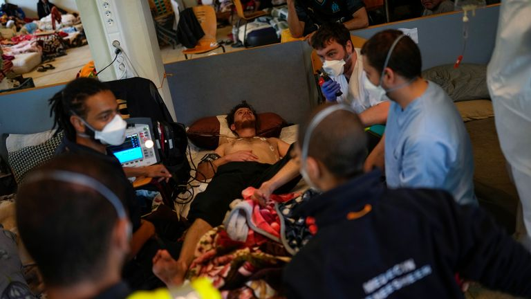 A Red Cross health worker calls an ambulance to transfer a man on hunger strike to a hospital as he occupies with others a big room of the ULB Francophone university in Brussels, Tuesday, June 29, 2021. More than two hundreds of migrants without official papers and who have been occupying a church and two buildings of two Brussels universities since last February, began a hunger strike on 23 May to draw the attention of Brussels authorities to their plight. (AP Photo/Francisco Seco)