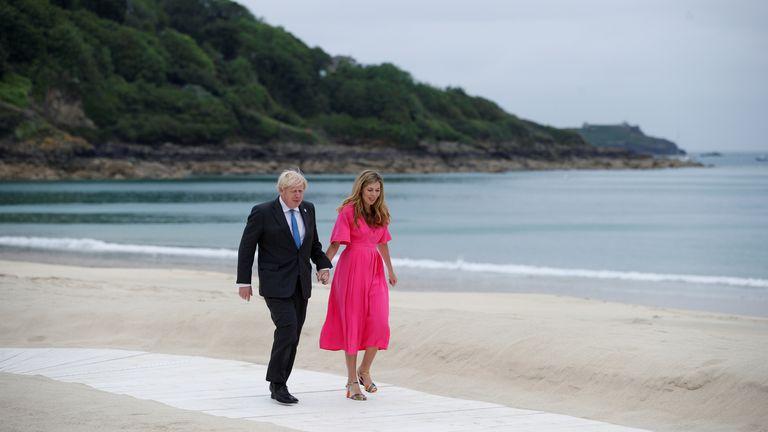 El primer ministro británico Boris Johnson y su esposa Carrie Johnson caminan en el resort durante la cumbre del G7 en Carbis Bay, Cornwall, Gran Bretaña, el 11 de junio de 2021. REUTERS / Phil Noble / Poole