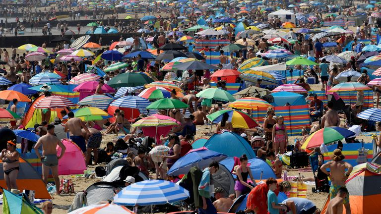 People enjoy the sunny weather at the Bournemouth Beach in Bournemouth