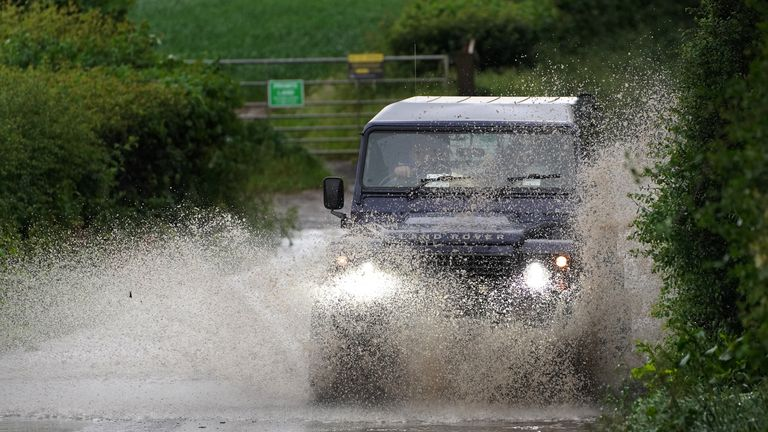 A car drives through a flooded road near Chesham, Buckinghamshire as rain and thunderstorms are set to sweep the South East in the coming days. Picture date: Friday June 18, 2021.