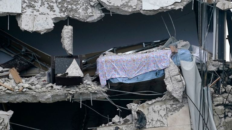 A bed dangles from part of the building that collapsed