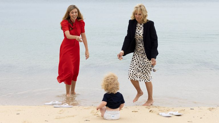 10/06/2021. Carbis Bay, United Kingdom. Carrie Johnson, wife of the Prime Minister speaks with First Lady of the United States Dr Jill Biden as Wilfred Johnson sits on the beach during the G7 leaders Summit in Carbis Bay Cornwall. Picture by Simon Dawson / No 10 Downing Street