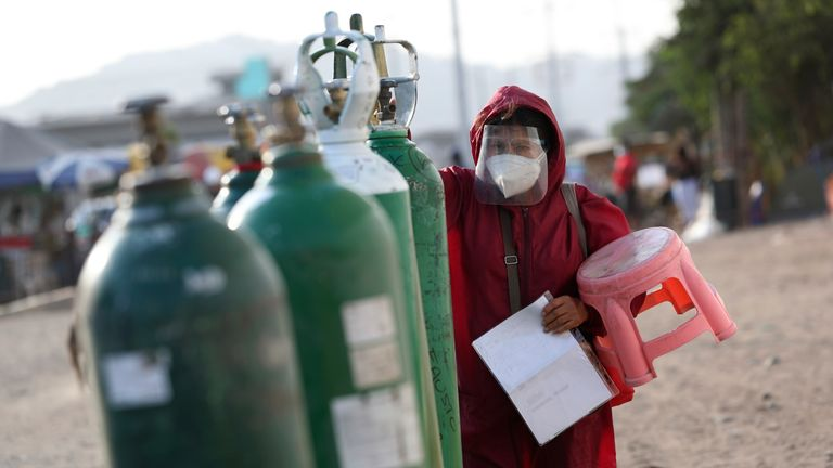 Sara Manrique checks her empty oxygen tank as she stands in line for a refill in the Villa El Salvador neighborhood of Lima. Pic: AP